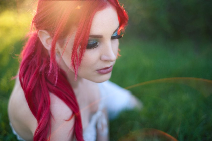 outdoor-boudoir-portrait-in-a-park-laying-down-pose-eyes-glancing-down-bright-red-hair-bright-green-eyeshadow-lens-flare-at-bottom-right-corner