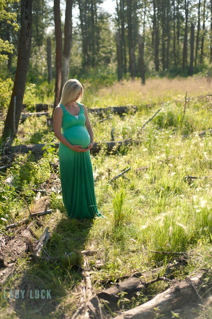 outdoor-maternity-portrait-wooded-area-pose-holding-the-belly-eyes-glancing-towards-the-belly