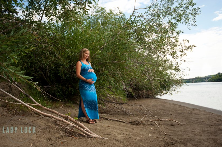 outdoor,maternity,session,in,saskatoon,along,the,river,bank,outside,the,delta,bessborough,client,wearing,a,blue,sarong,and,sandals,holding,her,belly,and,looking,off,toward,the,river,large,trees,in,the,background