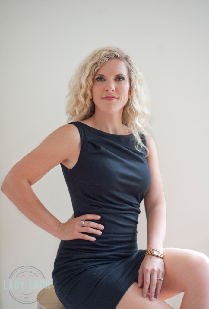 corportare-headshot-for-a-mortgage-broker-edmonton-alberta-blonde-female-wearing-a-black-dress-sitting-on-a-stool-one-hand-on-hip-the-other-draped-on-her-lap-smiling-at-the-camera
