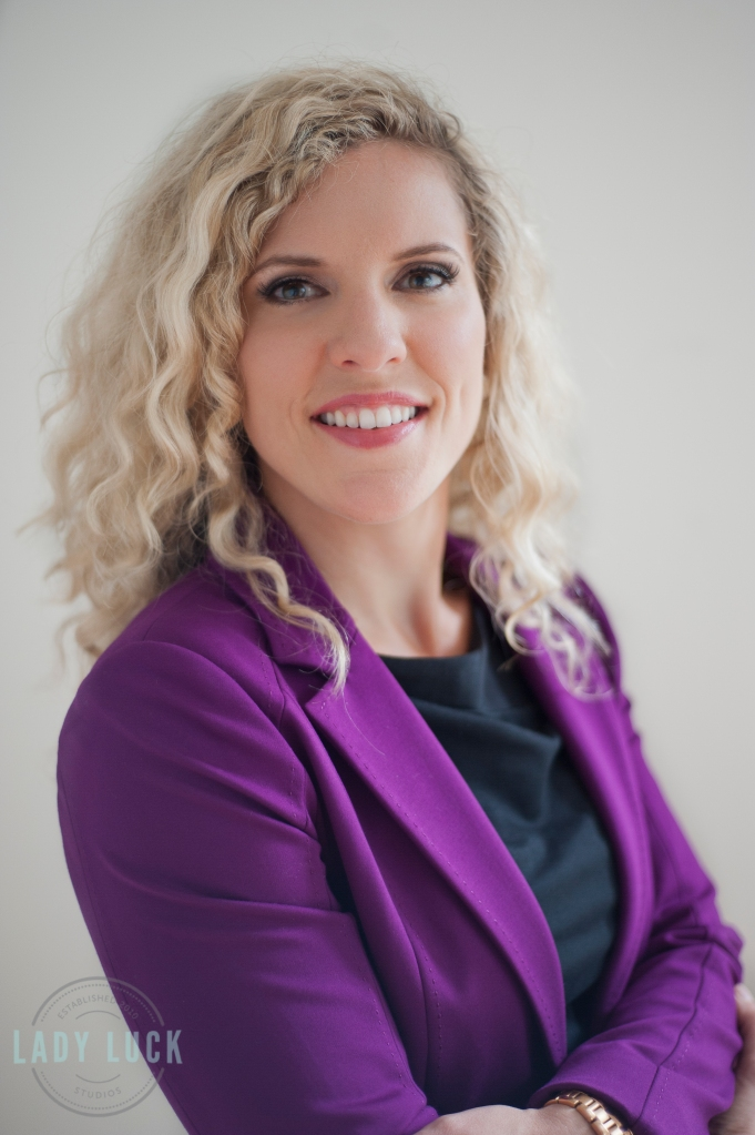 corporate-head-shot-for-mortgage-broker-edmonton-alberta-blonde-female-wearing-a-black-dress-with-a-purple-blazer-holding-onto-her-elbows-with-arms-crossed-smiling-at-the-camera