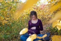 outdoor-maternity-session-blackmud-creek-edmonton-sitting-on-a-trail-with-fall-leaves-in-the-background