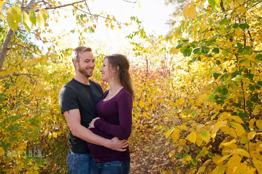 outdoor-maternity-session-edmonton-blackmud-creek-couple-hugging-and-smiling-at-each-other