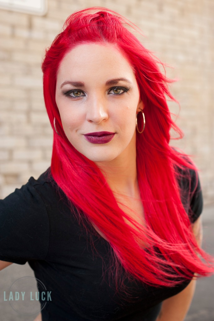 glamour-session-in-edmonton-wearing-a-black-top-with-red-hair-looking-at-the-camera