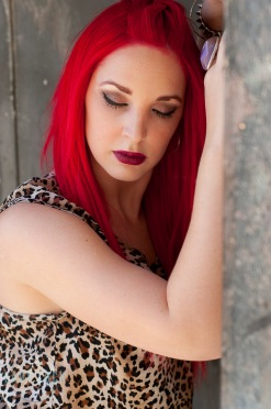 glamour-session-on-location-red-head-model-leaning-on-brick-wall-arms-up-over-her-head-looking-down-away-from-the-camer