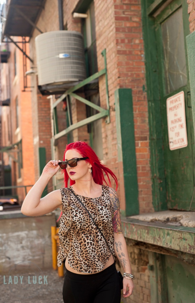 glamour-session-model-walking-towards-the-camera-looking-to-the-left-taking-off-her-sunglasses-brick-building-in-the-background