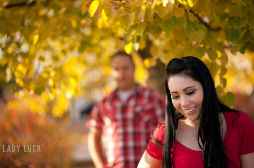 outdoor-couples-portrait-yellow-leafs-on-the-tree-girlfirend-in-the-foreground-smiling-looking-down-boyfriend-in-the-background