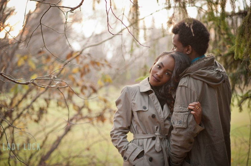 outdoor-fall-couples-portrait-man-facing-away-from-camera-women-leaning-in-his-shoulder-looking-into-the-camera-located-in-the-trees-with-green-grass-in-the-background