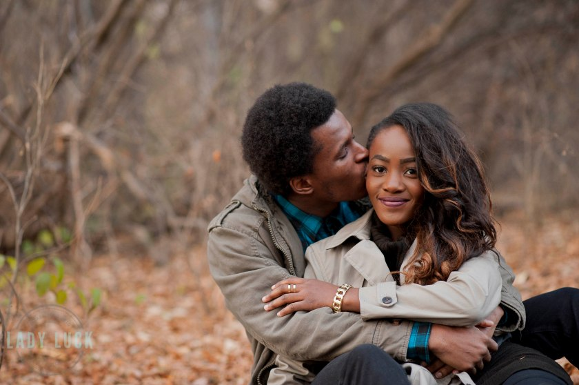 outdoor-couples-portraits-in-the-fall-couple-sitting-in-eachothers-arms-he-is-kissing-her-temple-and-she-is-looking-at-the-camera