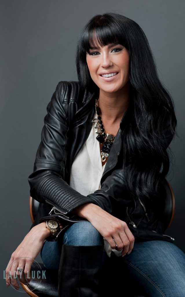 corporate-headshots-edmonton-alberta-for-llashbar-jesse-is-wearing-blue-jeans-a-white-blouse-and-black-leather-jacket-she-is-sitting-on-a-black-chair-with-her-wrists-crossed-over-her-knee-smiling-at-the-camera