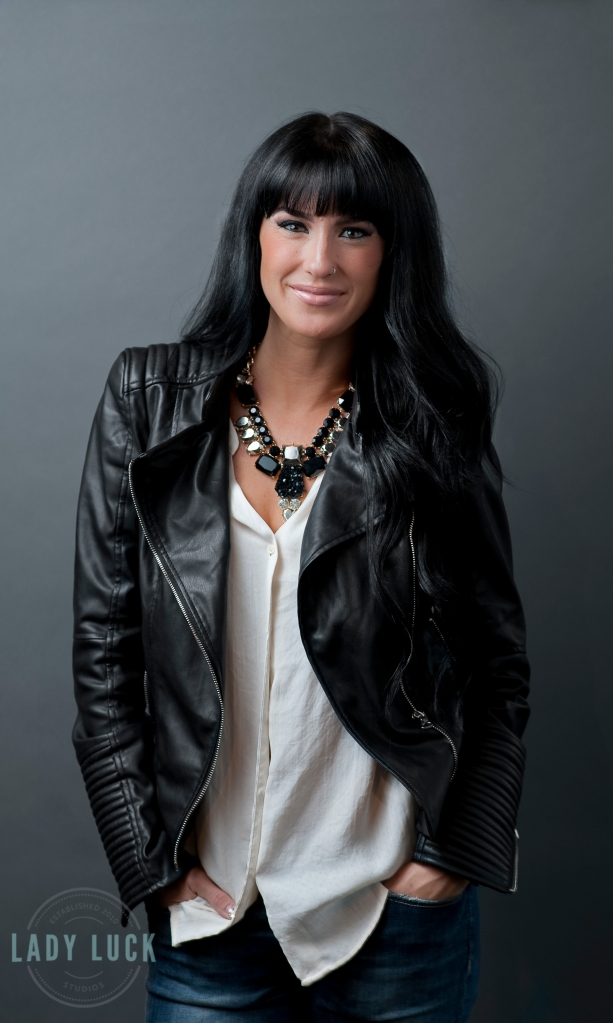 corporate-headshot-in-edmonton-alberta-for-llashbar-jesse-is-wearing-blue-jeans-a-white-blouse-and-black-leather-jacket-she-is-in-a-comfortable-standing-position-with-her-hands-in-her-pocket-smiling-at-the-camera