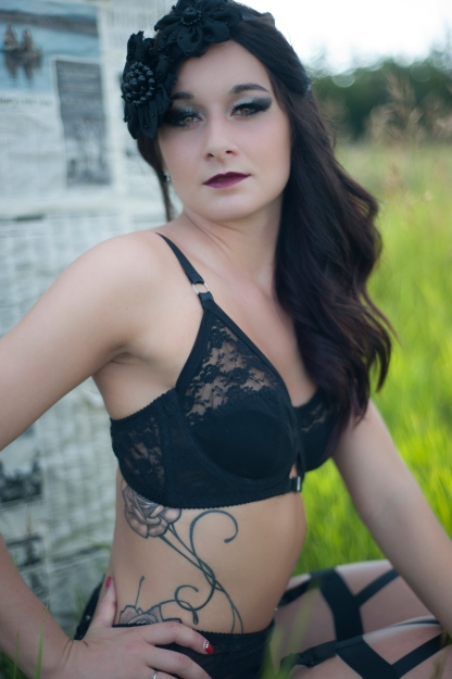 outdoor-boudoir-session-in-edmonton-black-lingerie-with-black-headpices-women-standing-in-green-grass-with-trees-behind-her