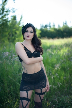 putdoor-boudoir-session-in-stalbert-alberta-black-lingerie-black-head-piece-women-standing-in-green-grass-looking-at-the-camera