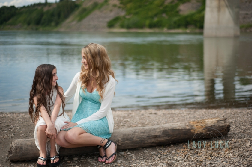 sisters-sitting-on-a-log-near-the-river-in-edmonton-looking-at-eachother
