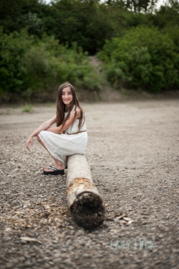 outdoor-glamour-portrait-of-teenager-sitting-on-a-log-beside-the-river-in-edmonton