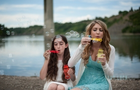 sisters-photo-session-blowing-bubbles-at-the-camera-sitting-on-a-log