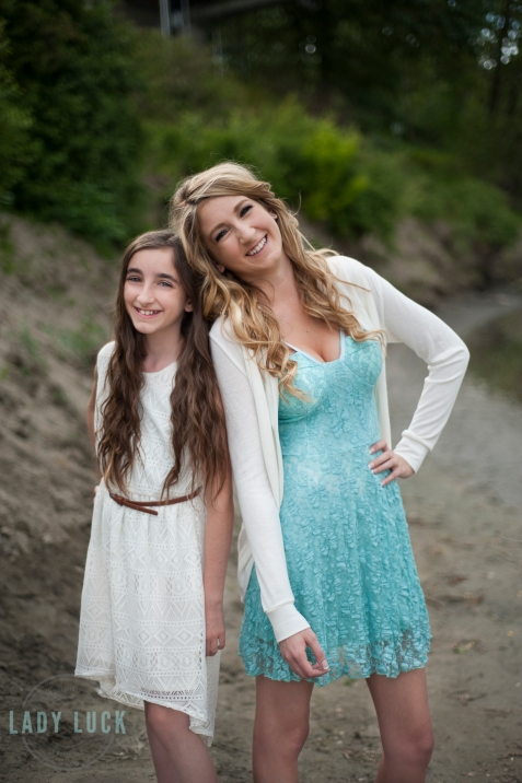 sisters-outdoor-photo-shoot-north-saskatchewan-river-edmonton-posing-with-heads-leaned-into-eachother