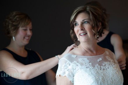 bride-looking-out-the-window-bridesmaids-doing-up-her-dress