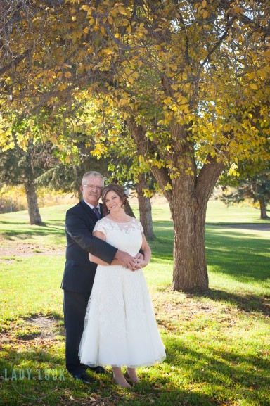 bride-and-groom-holding-each-ther-under-a-tree-in-the-fall