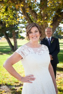 bride-in-the-foreground-smiling-at-the-camera-groom-in-the-background