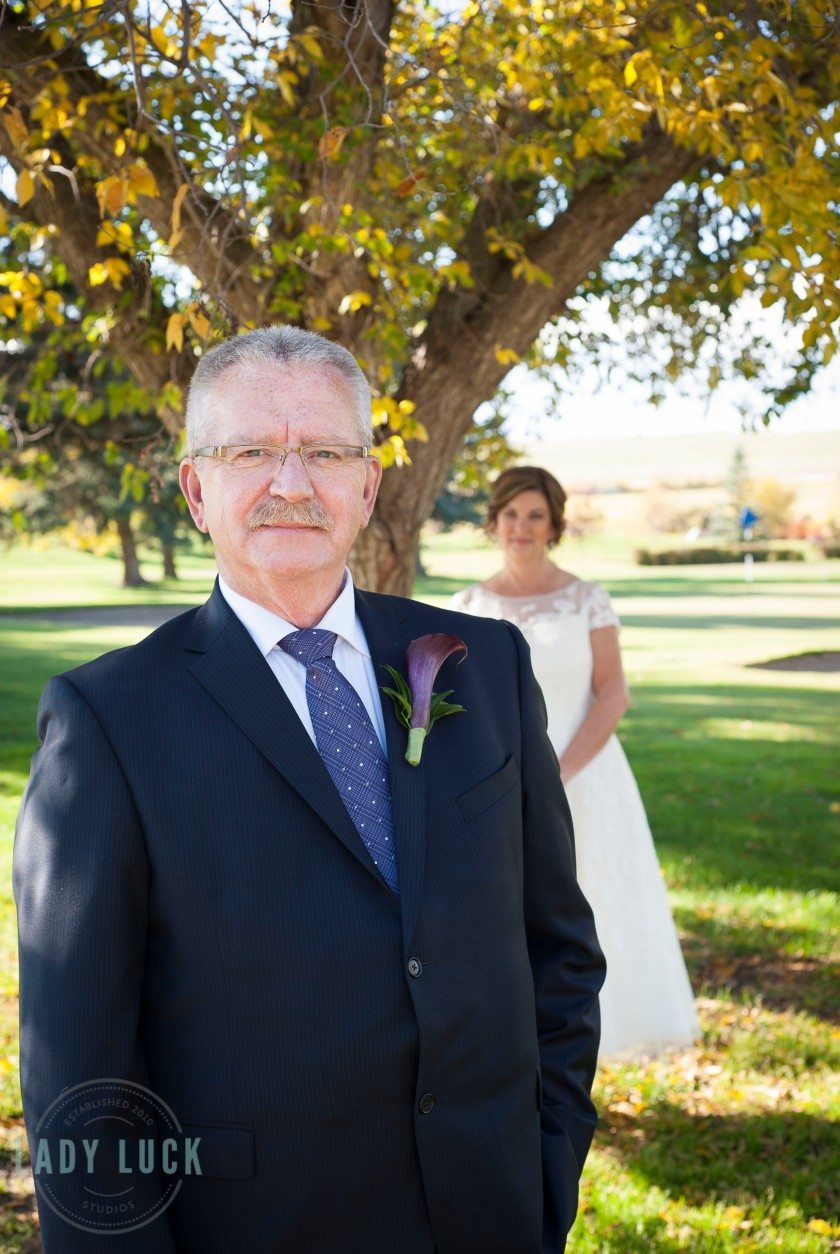 groom-in-the-foreground-smiling-at-the-camera-bride-in-the-background