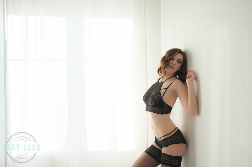 boudoir-portrait-women-standing-against-the-wall-arms-up-wearing-black-lingerie