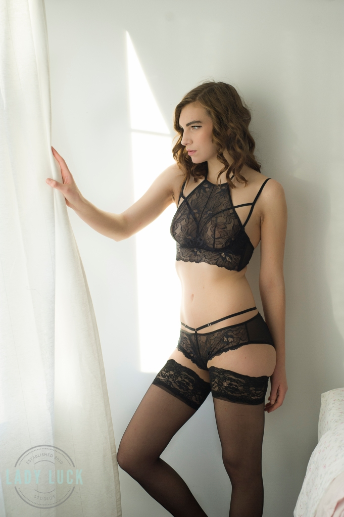 woman-standing-infront-of-window-in-black-lingerie-holding-the-curtain